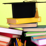 Books and magister cap against school board on wooden table on green background